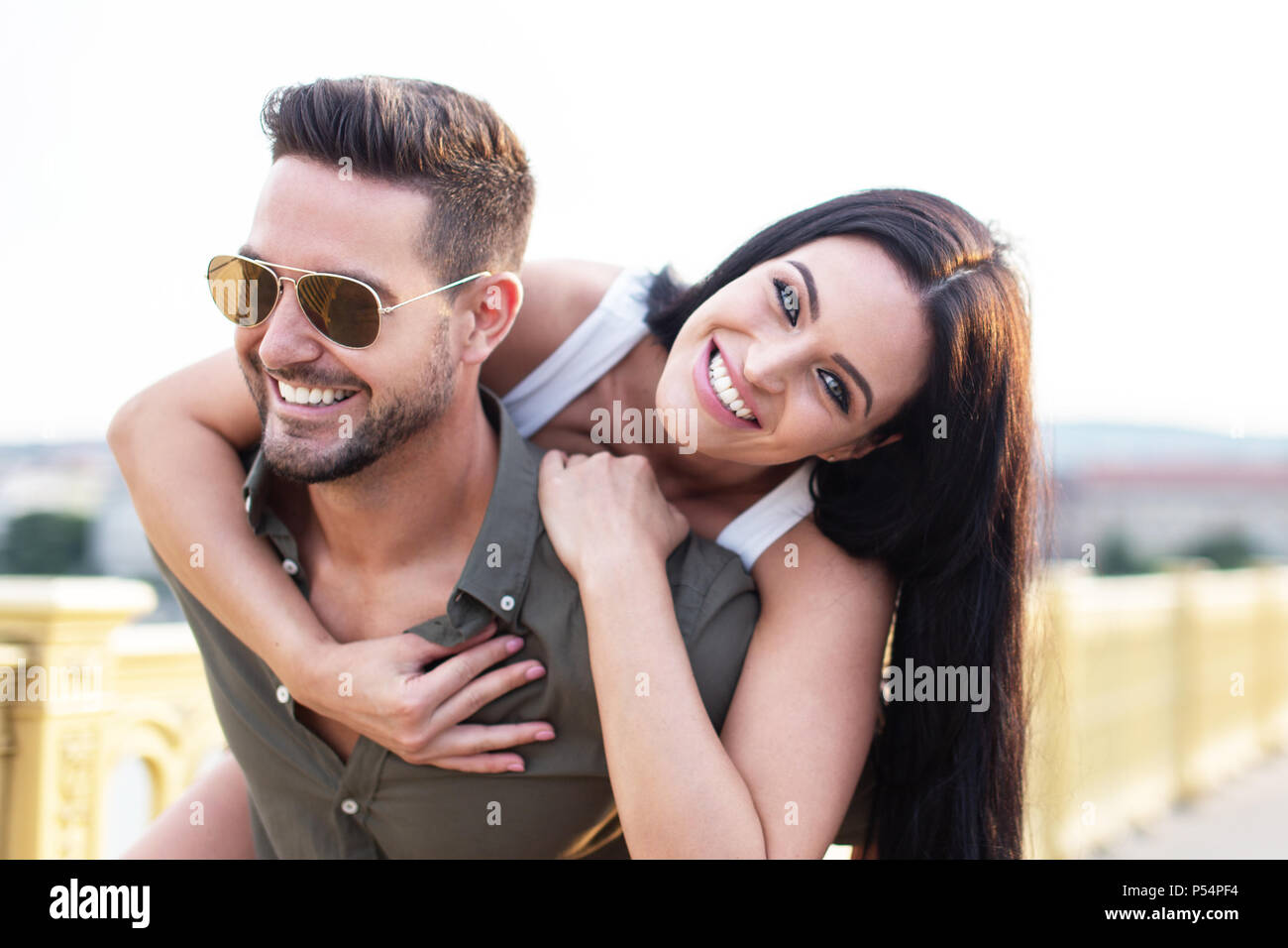 Happy young couple have fun outdoors, piggyback, love - Stock Image