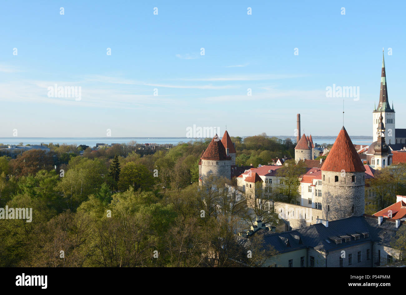 Medieval wall and towers around the Old Town of Tallinn, Estonia, meet wooded parkland. Tallinn Bay lies beyond. - Stock Image