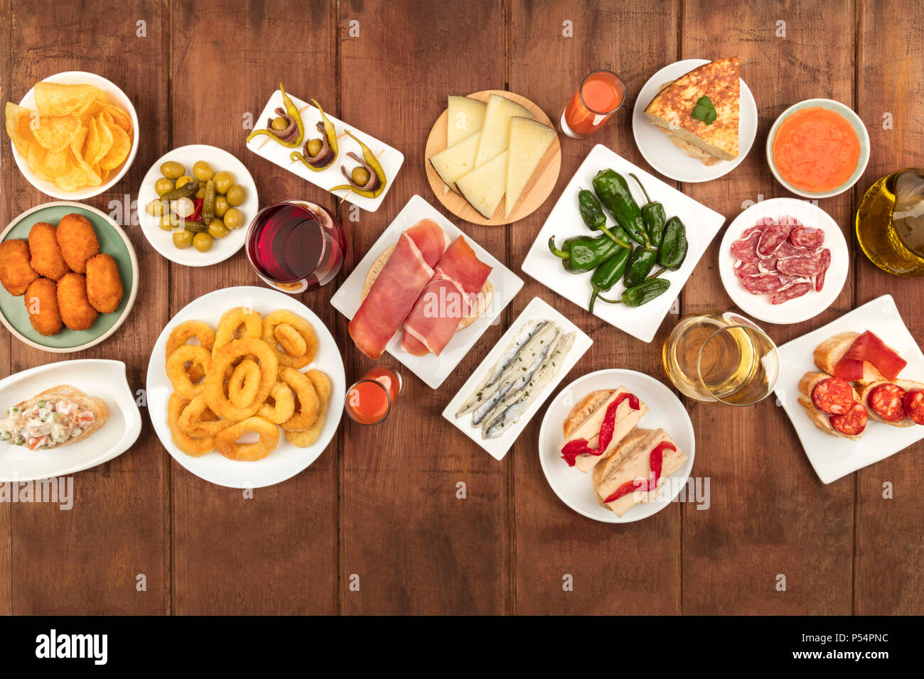 Overhead photo of many different Spanish tapas foods, shot from above on a dark rustic background with a place for text. Jamon, gazpacho, cheese, etc - Stock Image