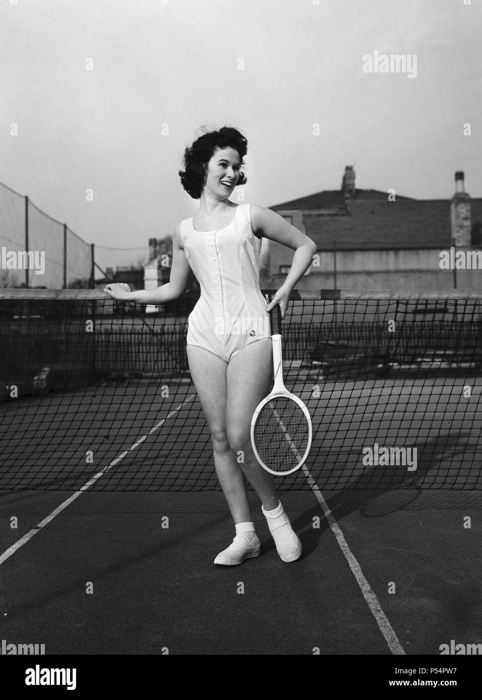 Model Norma Parnell wearing a white cotton button romper with camisole top, worn beneath a brief flared skirt by designer Fred Perry.  8th April 1957. - Stock Image