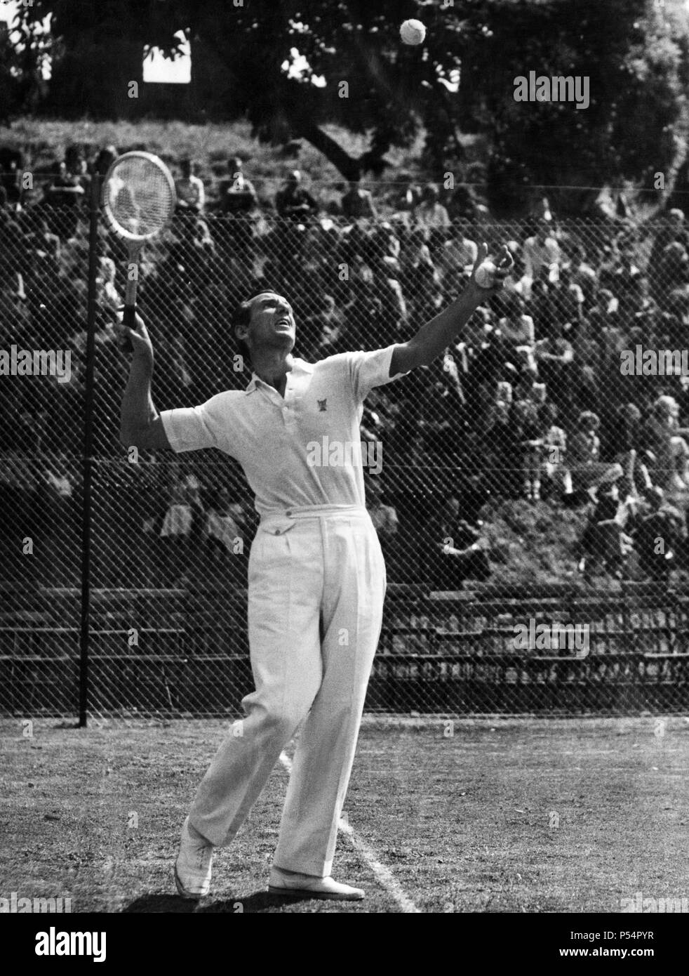 Fred Perry  Tennis player demonstrates the service play during his exhibition at Cardiff Castle grounds. 8th July 1949 - Stock Image