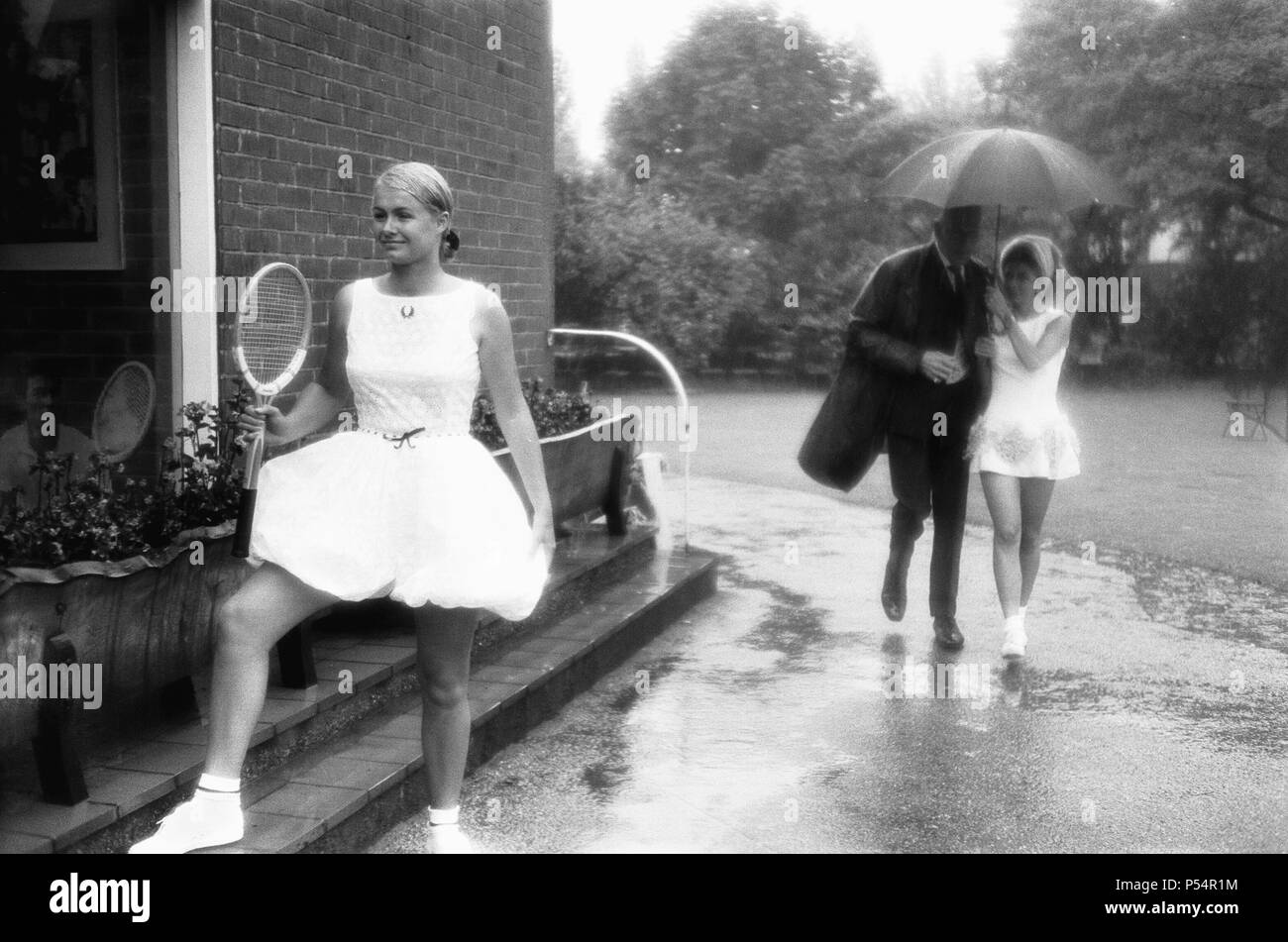 Lea Pericoli v Susanna Alexander at the rain soaked pre Wimbledon garden party at the Hurlingham Club. The girls were there braving the deluge, to show off their new tennis dresses. And Italy's Lea, that's her sharing an umbrella with designer Teddy Tinling, wouldn't pose with Australian girl Susanna. Lea's dress you see is a Tinling creation. And Susanna is wearing a Fred Perry bloomer outfit. 26th June 1967 - Stock Image