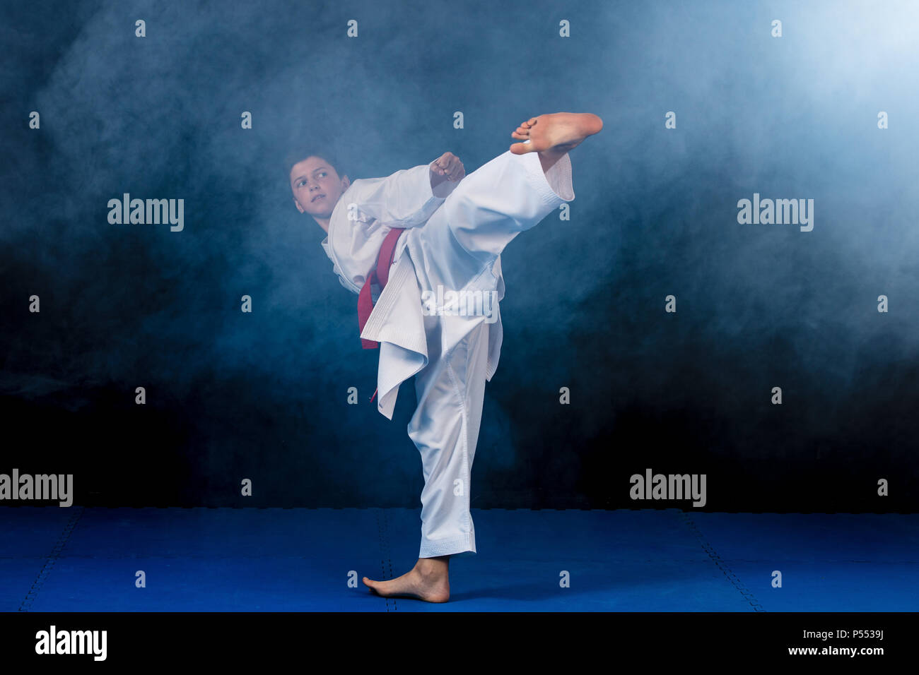 Pre-teen boy doing karate on a black background with smoke Stock Photo
