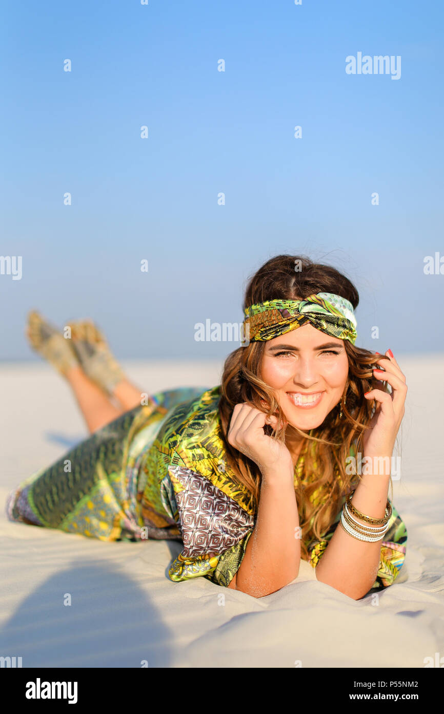 Young smiling girl wearing green beach robe lying on white sand. - Stock Image