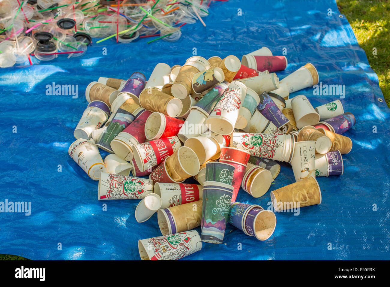 Piles of non-recyclable cups and straws destined for the landfill. - Stock Image