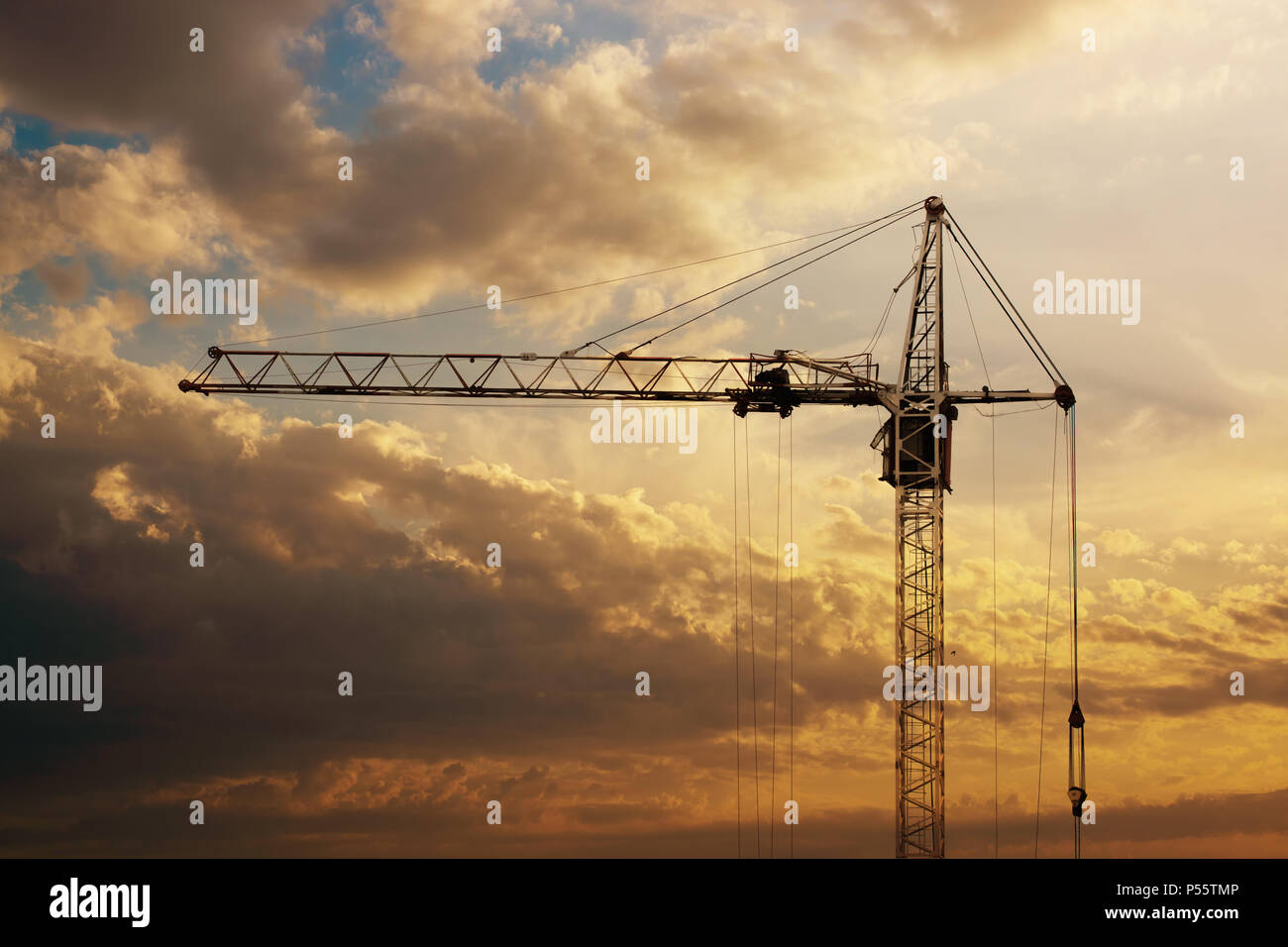 Tower crane on a construction site at sunrise. - Stock Image