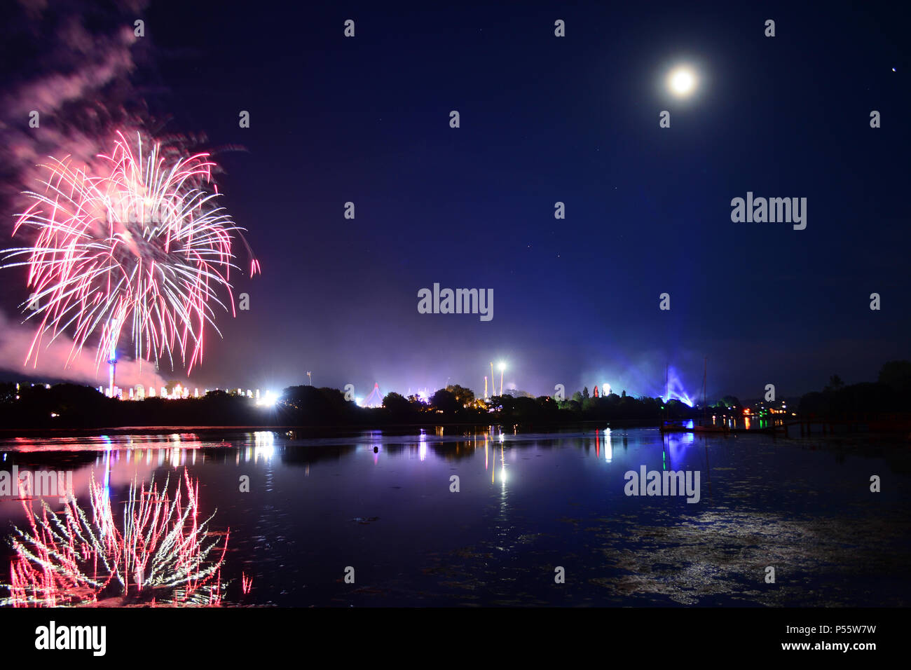 Newport, Isle of Wight, UK. Fireworks and a near full moon herald the end of the last day of the Isle of Wight Festival 2018. Stock Photo