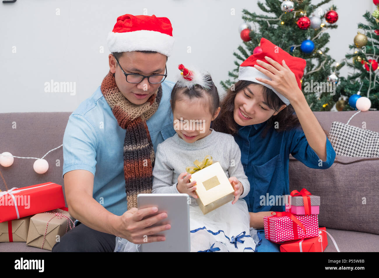 Happy family Asia selfie with tablet at sofa,father and mother wear santa claus hat give Christmas gift box to child at house xmas party,Holiday celeb - Stock Image