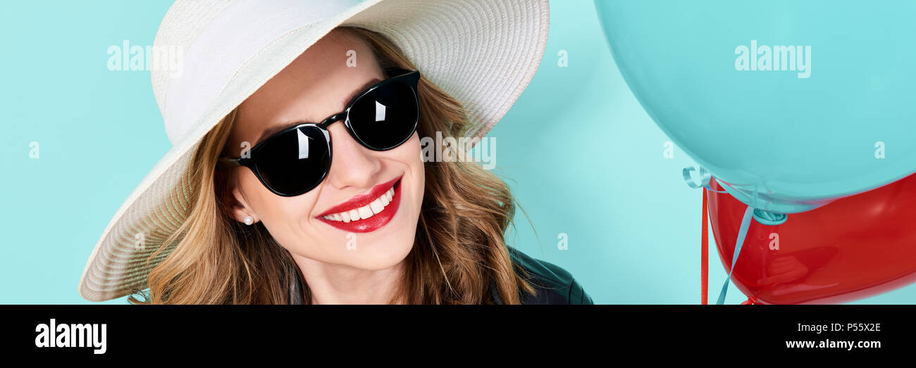 11a28a5bdf Beautiful woman in summer hat and sunglasses holding balloons. Attractive  cool young woman fashion portrait over pastel blue banner background.