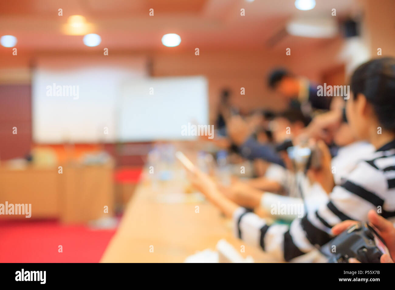 blurred conference, press media, meeting room, lecture classroom with long tables and audience background - Stock Image