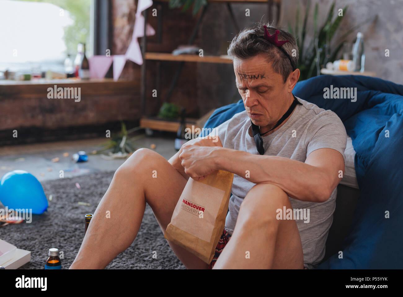 Attentive mature man unpacking recovery kit - Stock Image