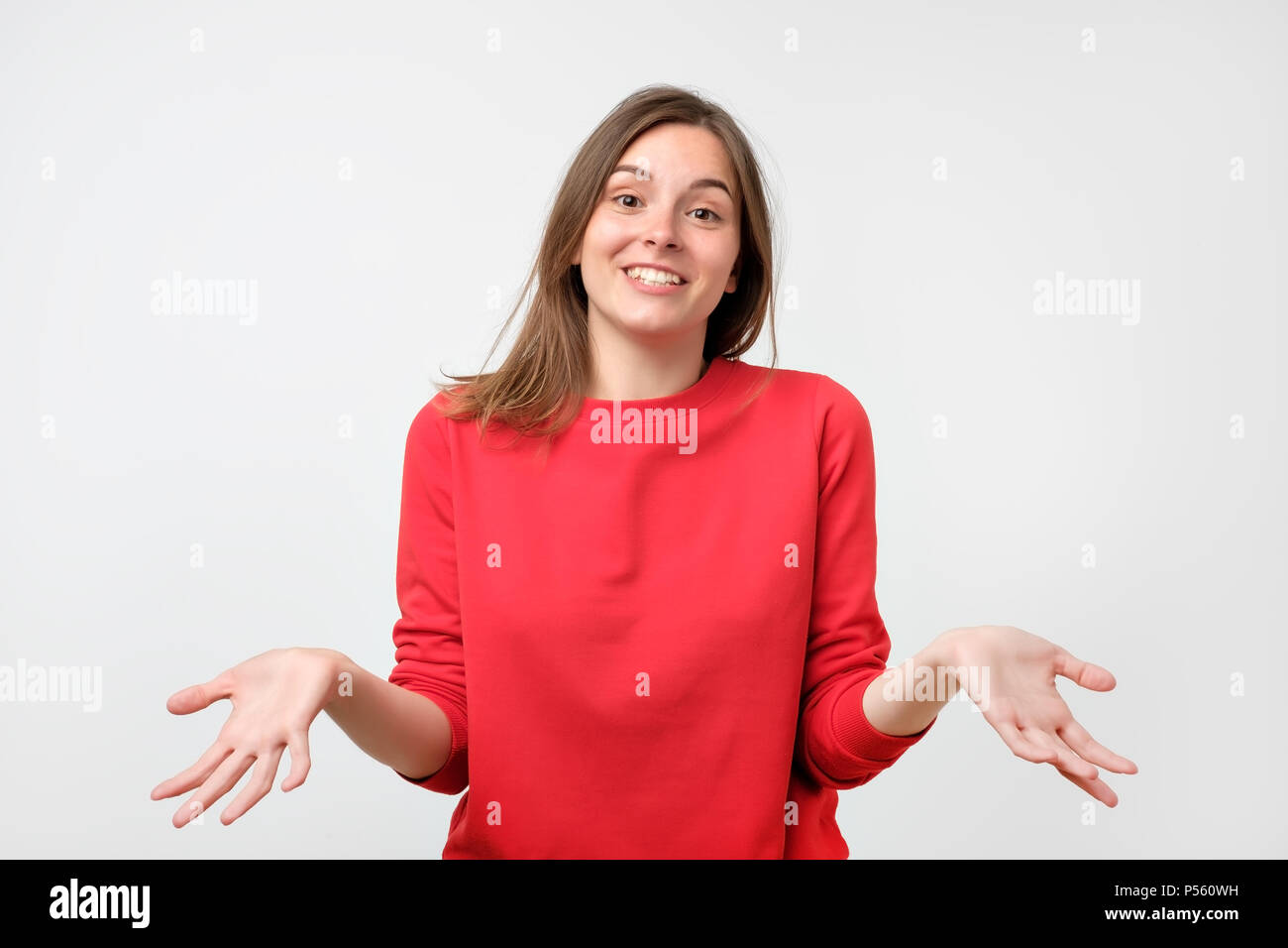 Young woman in red sweater standing disorientated bewildered isolated on gray wall background. Decision making concept. Stock Photo