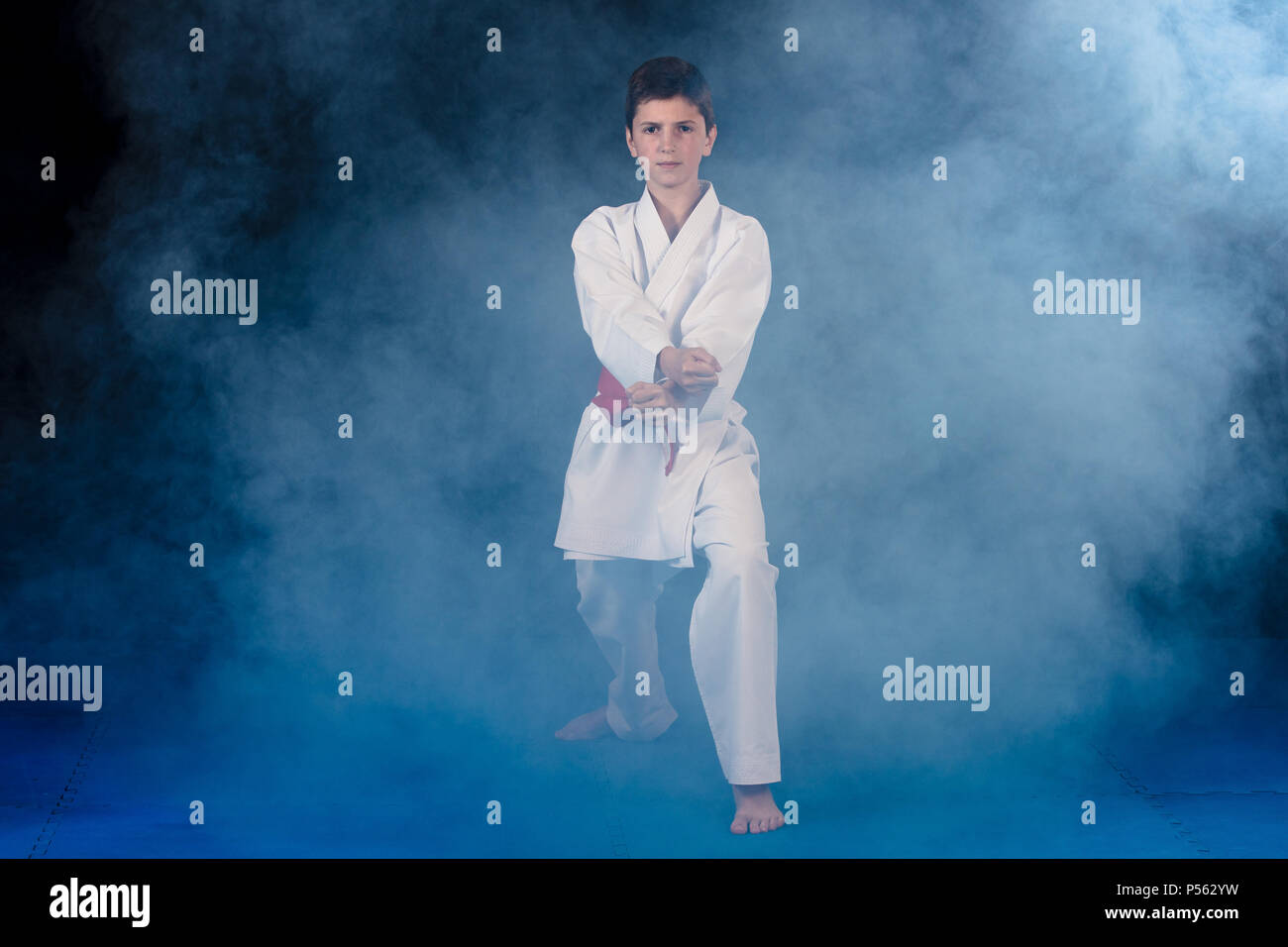 Pre-teen boy doing karate on a black background with smoke - Stock Image
