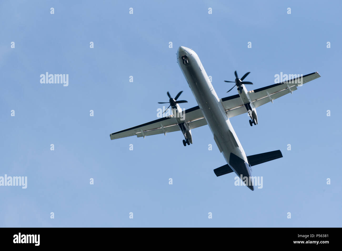 A Twin engined passenger aircraft with undercarriage and flaps extended for landing - Stock Image