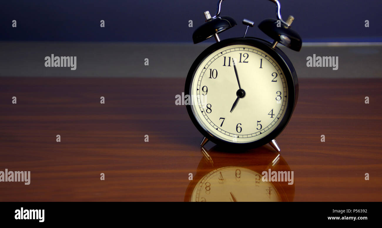 Classic style alarm clock on table with reflection - Stock Image