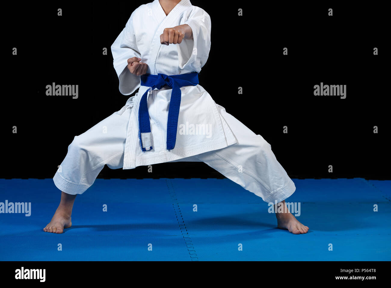 Pre-teen boy doing karate on a black background - Stock Image