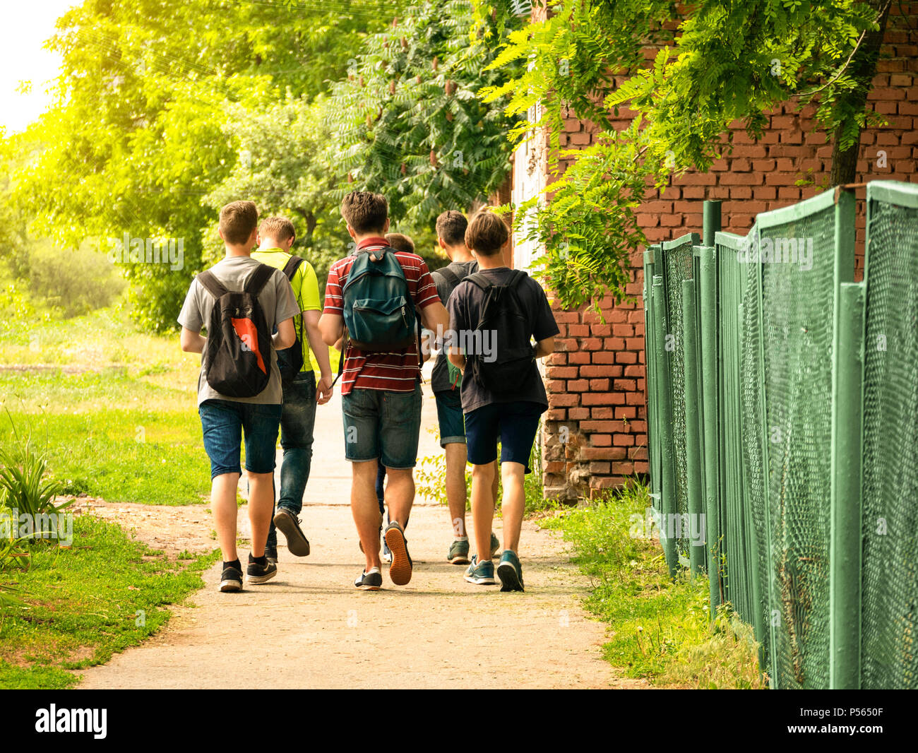 Backs of schoolchildren with colorful rucksacks moving to the school in the street - Stock Image
