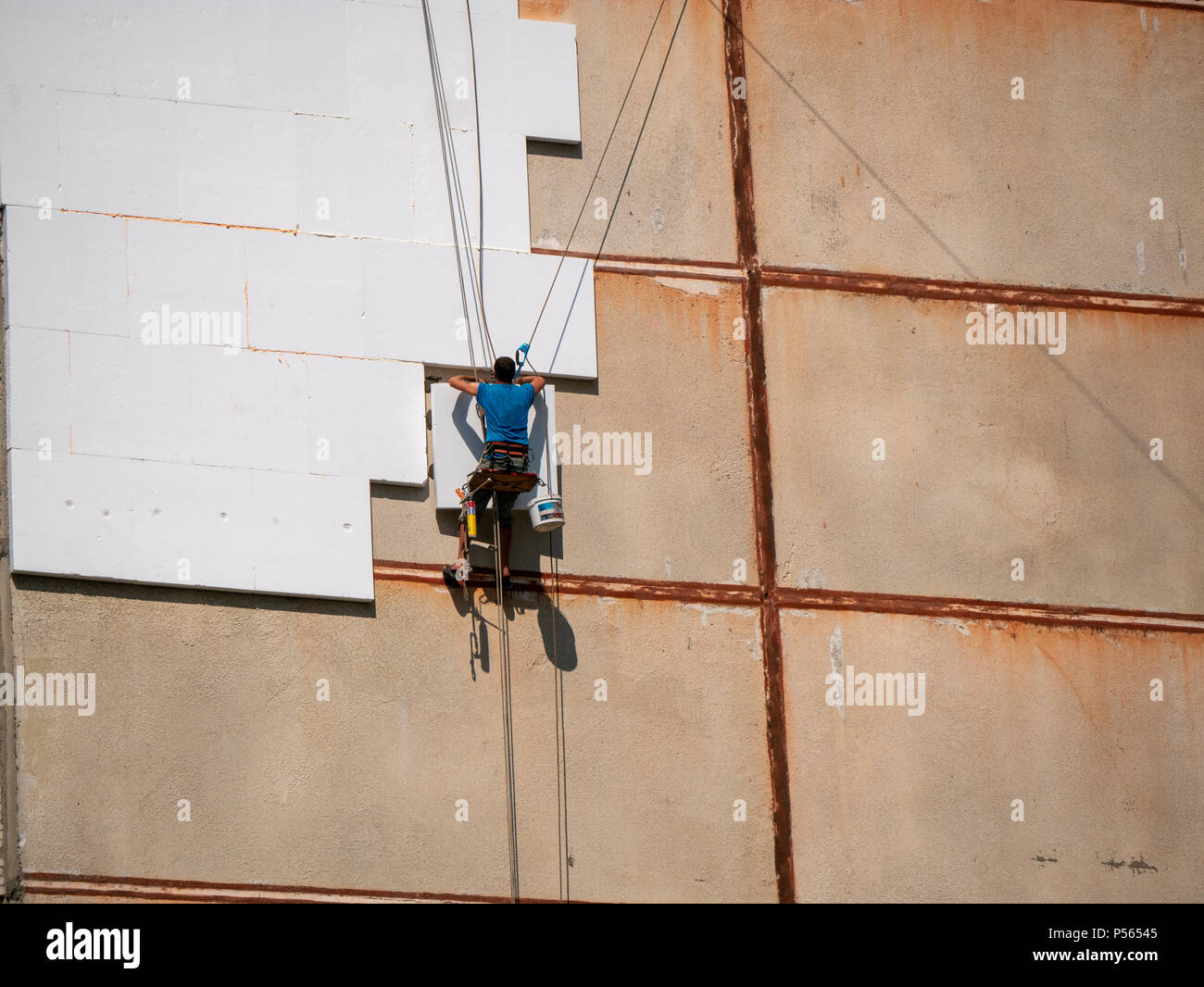 Insulation and Energy Saving Technology Concept. Worker Making Building with heat insulated facade - Stock Image