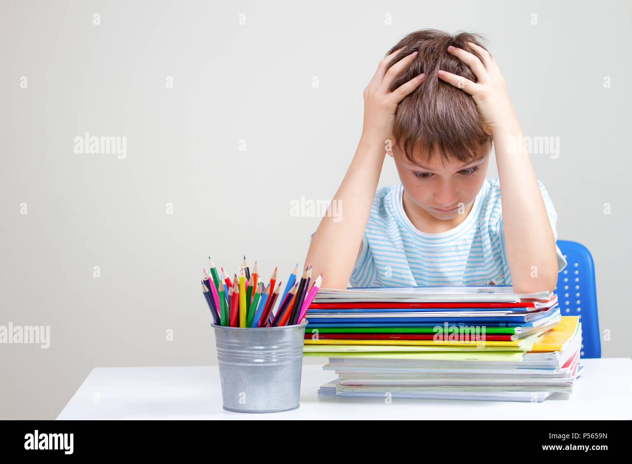 The boy sitting and looking in to books and notebooks. Education, school, learning difficulties concept - Stock Image