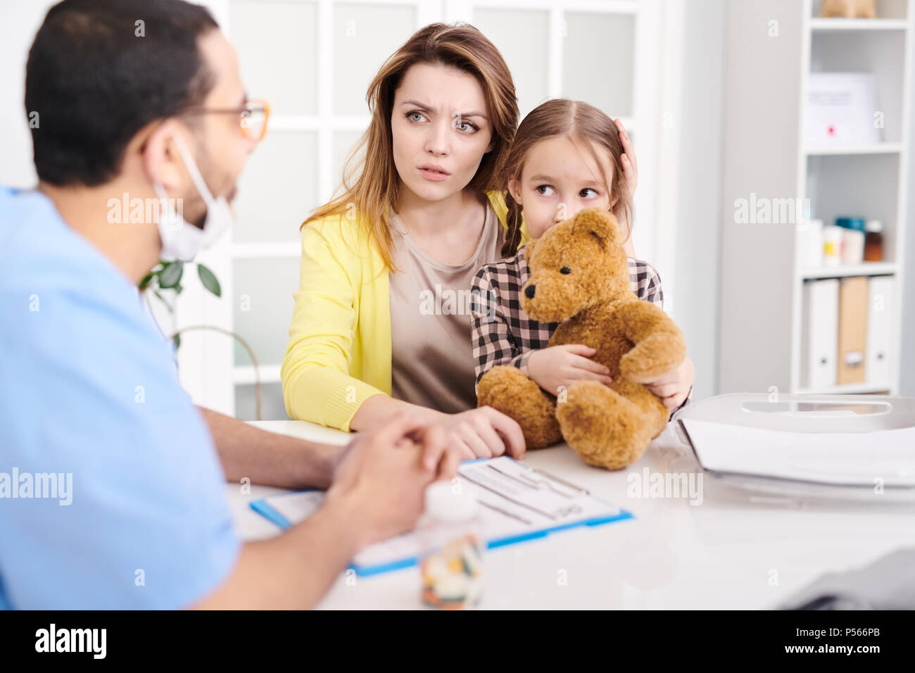 Concerned Mother in Doctors Office - Stock Image