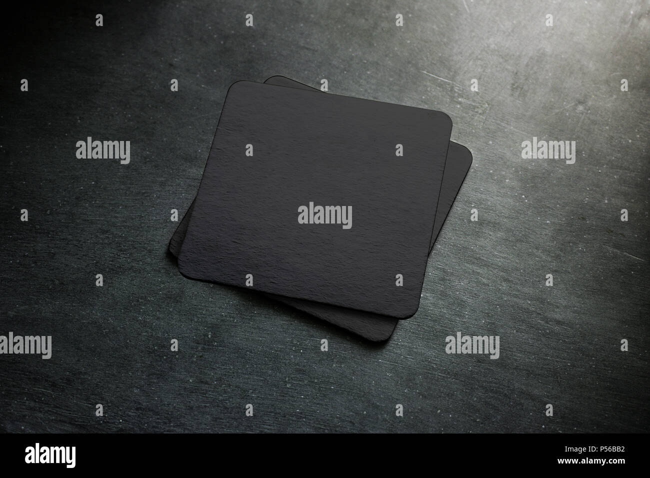 Blank black beer coaster stack mock up, top view, lying on the textured background. Squared clear can mat design mockup isolated. Quadrate cup rug display Stock Photo