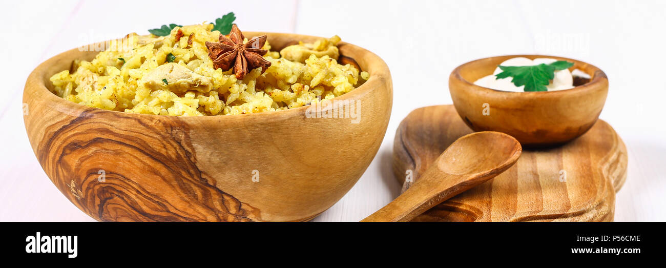 Indian biryani with chicken, yogurt and spices in a plate on a wooden table. New Year's, Christmas dish - Stock Image