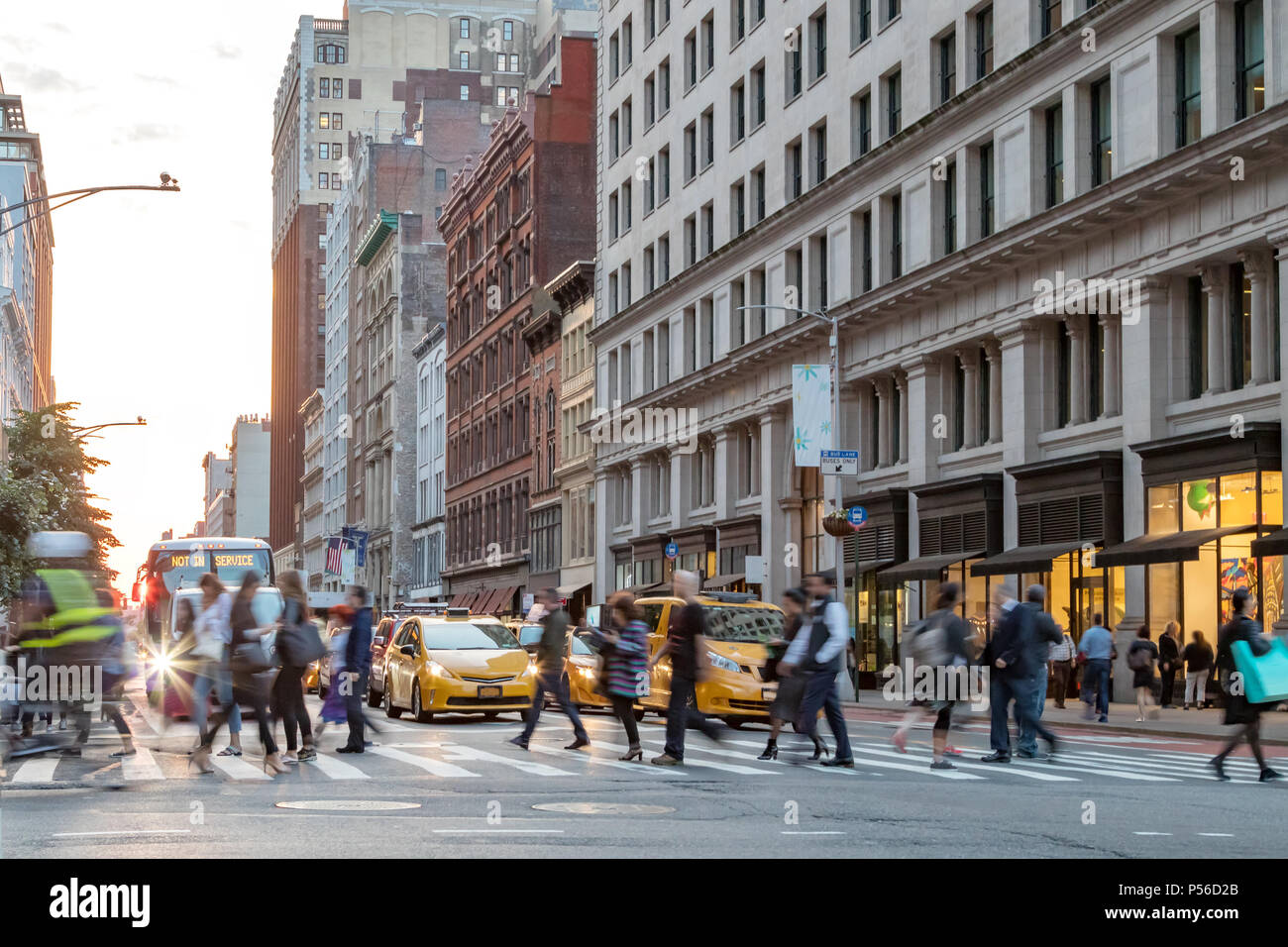 Fast paced street scene with people walking across a busy intersection on Broadway in Manhattan New York City - Stock Image