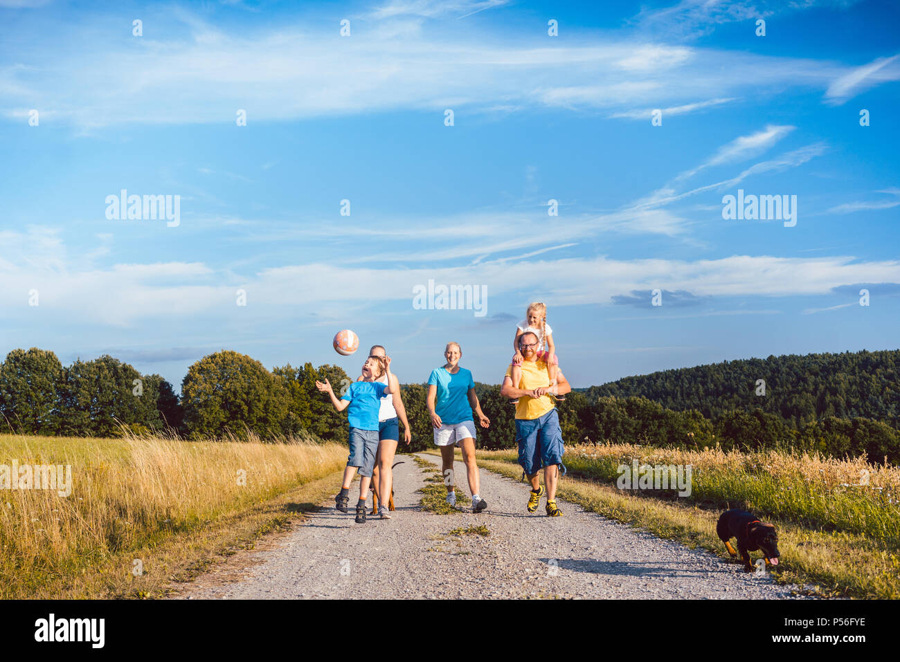 Family walking their dog on a dirt path - Stock Image