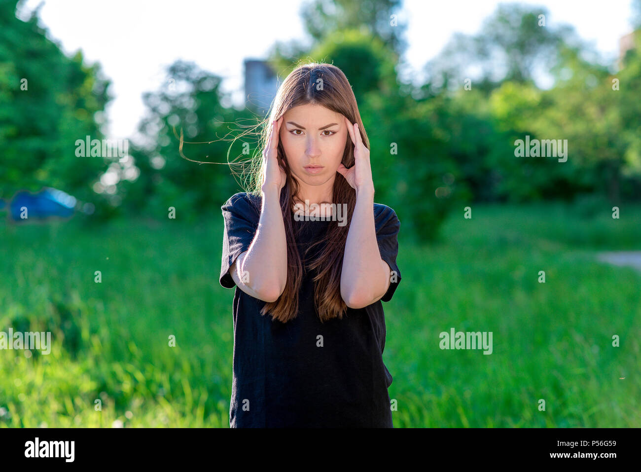A brunette woman is Asian. Holds his hands near the head. Emotions are a strong headache migraine. In the summer in the park in the fresh air. - Stock Image