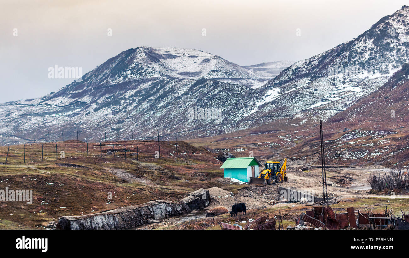 An Earth mover parked beside a garbage house at Nathang valley covered with snow. - Stock Image