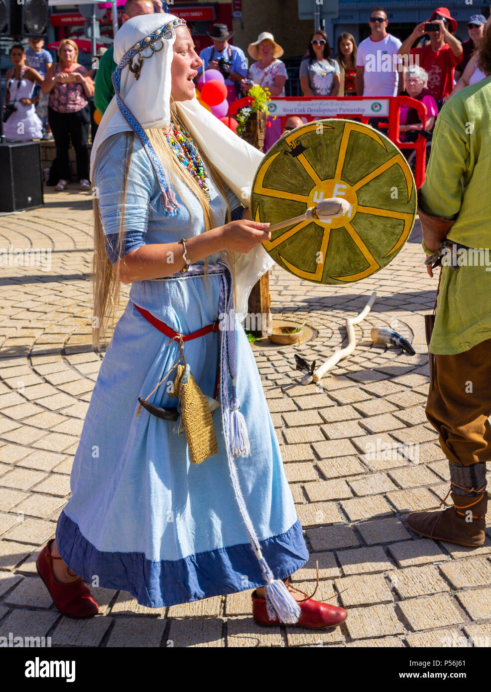 female in  Viking dress or costume playing a hand held drum as part of mid summer ceremony re enactment in bantry west cork, ireland - Stock Image
