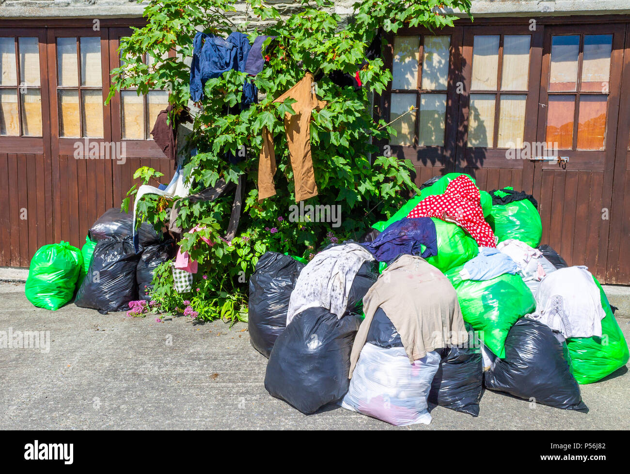recycled clothing in plastic sacks waiting to be collected for recycling - Stock Image