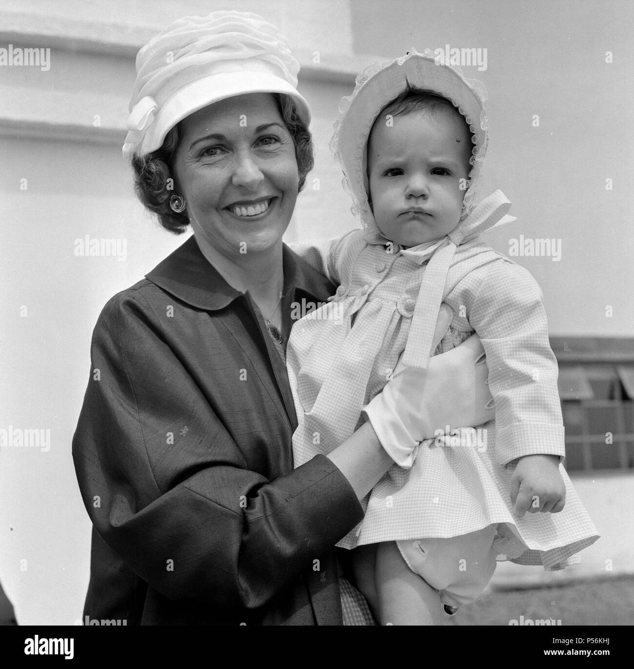 Barbara Riese, (wife of tennis player Fred Perry) pictured with their daughter Penny who is 8 months old as this picture was taken.  They are pictured arriving at London Airport.  Picture taken 5th June 1959 - Stock Image