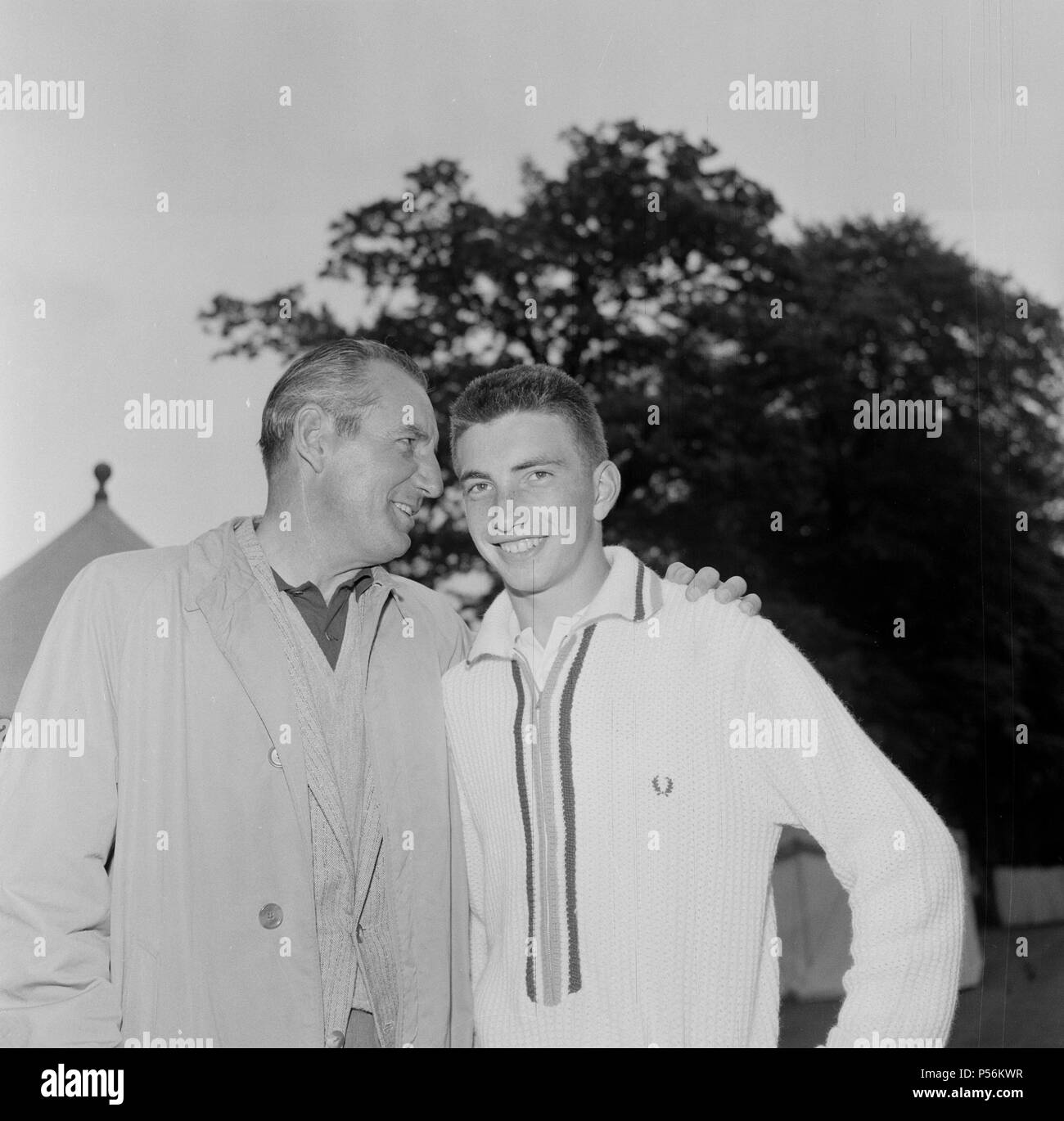 Fred Perry (left) former Wimbledon champion talking with Stan Matthews Junior who is Junior British Champion during a tennis tournament at Didsbury, Manchester  Picture taken 7th June 1961 - Stock Image