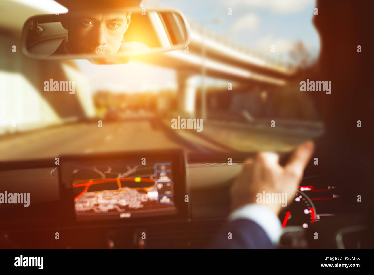 Man driving car and looking into rear view - Stock Image