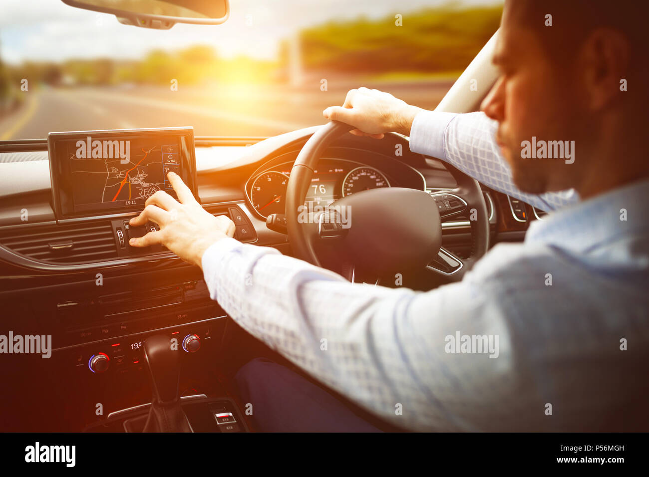 Man using navigation system in car - Stock Image