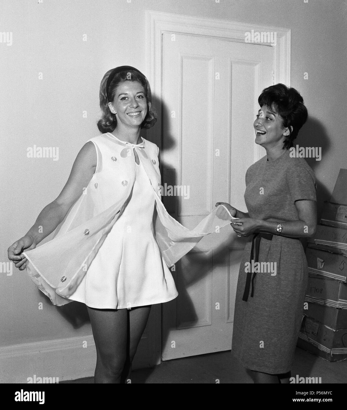 Pre Wimbledon Fashions Photoshoot. Lea Pericoli wearing a princess line tennis dress in tricel with petal cutouts on neckline topped by a nylon organza cloack embroidered with a gold laurel wreath motif. She is showing her dress to S. Lazzarino who will also be wearing it when they play in the Doubles at Wimbledon. 20th June 1963. - Stock Image