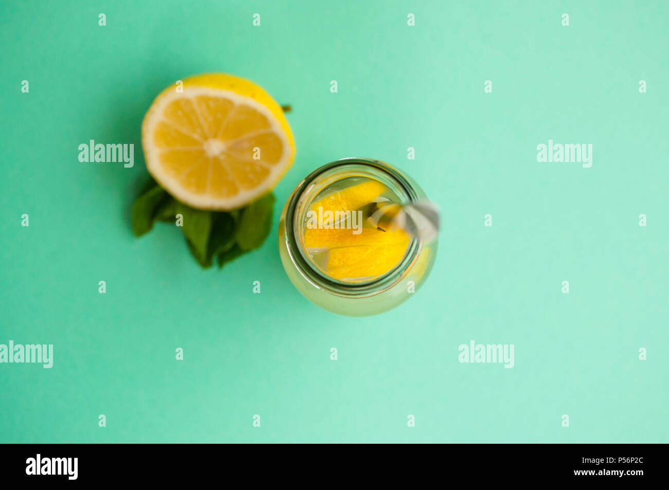 Top view of mason jar glass of lemonade or mojito with lemons and mint on turquoise background. Stock Photo