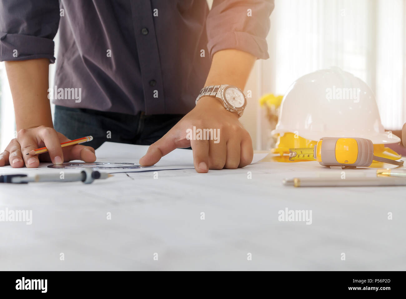Architect or engineer using pencil and protractor working on blueprint, architectural concept - Stock Image