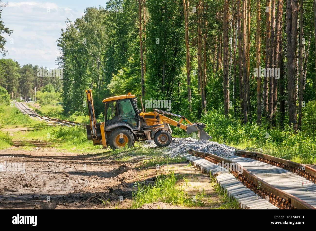 Yellow excavator pours gravel on the construction of the railway in the forest - Stock Image
