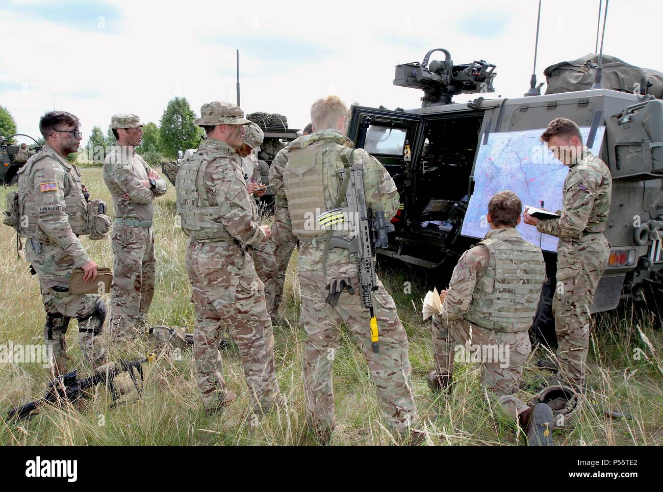Lance Cpl. Ben Tong, from 1st The Queens Dragoon Guards, part of Battle Group Poland briefs U.K. and U.S. Army soldiers on enemy intel during Saber Strike 18 in Bemowo Piskie Training Area, Poland on June 11, 2018, June 12, 2018. Saber Strike 18 is the eighth iteration of the long-standing U.S. Army Europe-led cooperative training exercise designed to enhance interoperability among allies and regional partners. (Michigan Army National Guard photo by 1st Lt. Erica Mitchell/ released). () - Stock Image