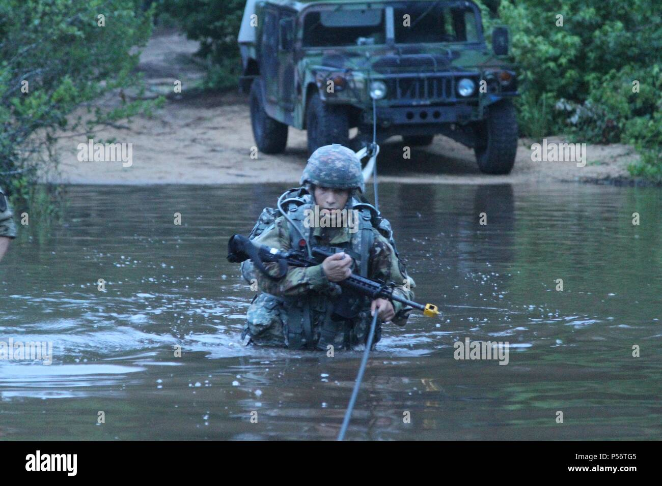 U.S. Army Reserve Spc, June 12, 2018. Nicholas Cholula, a combat documentation production specialist representing the 311th Signal Command Theater Support Unit crosses the river during the ruck march event at the 2018 U.S. Army Reserve Best Warrior Competition at Fort Bragg, North Carolina, June 12, 2018. The grueling, multifaceted competition evaluated U.S. Army Reserve Soldiers in the ruck march, the Excellence in Competition pistol range, the German Armed Forces Proficiency Badge and several other events with more challenges to come. (U.S. Army Reserve photo by Sgt. Rachel A. Leis) (Release - Stock Image
