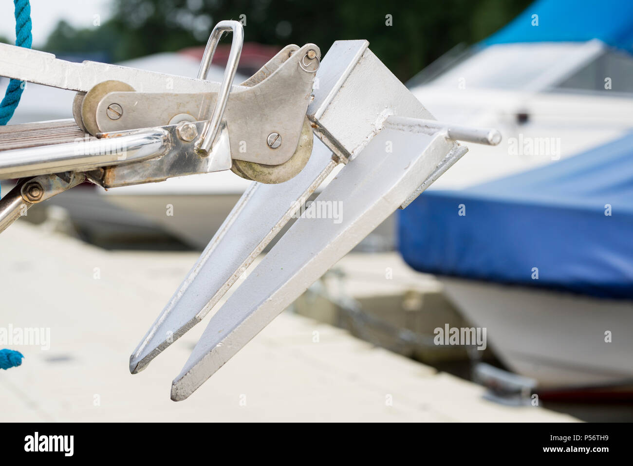 A anchor on a boat which lie on the pier in sun shine - Stock Image