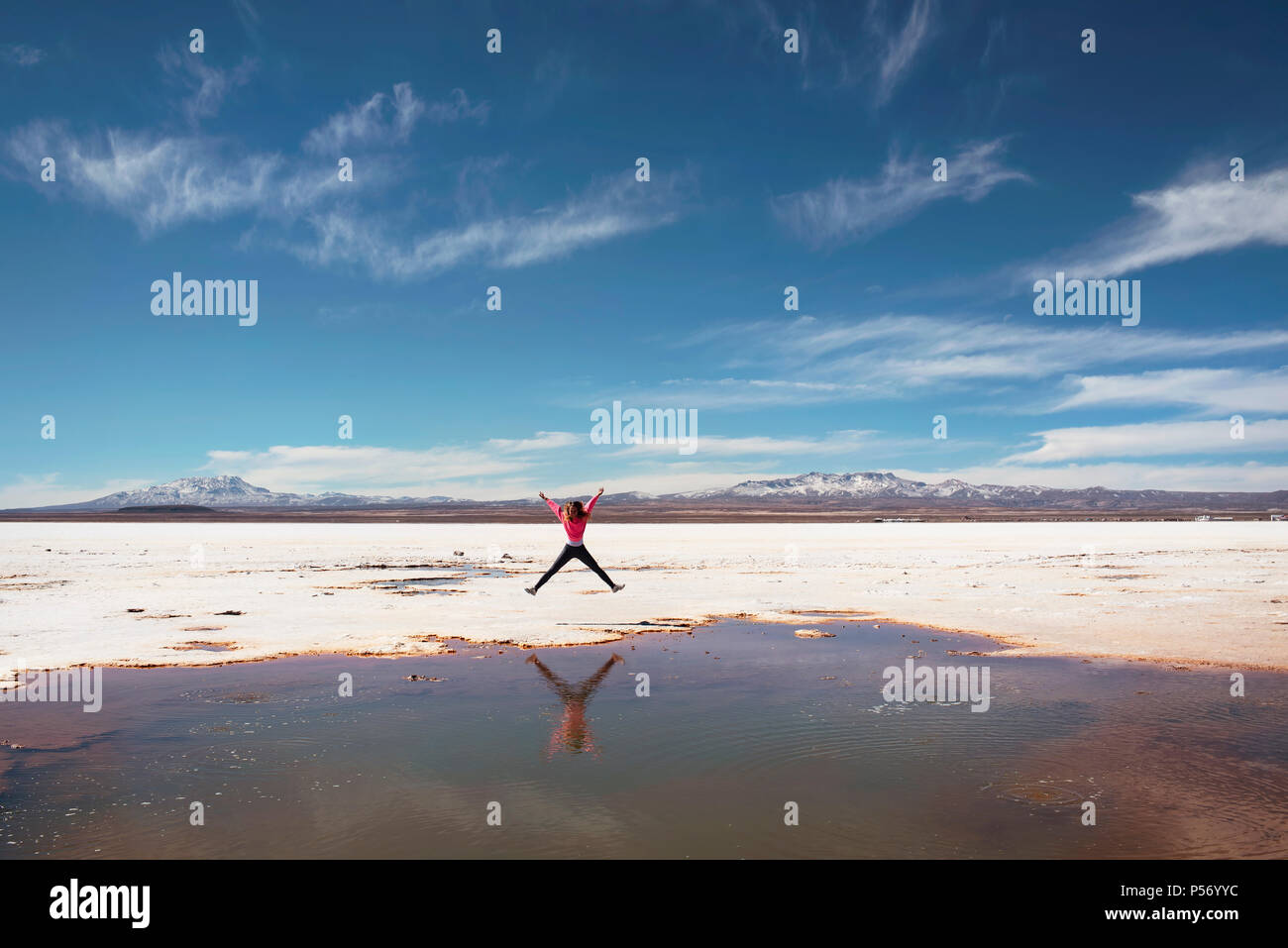 Happy jumping on the side of a natural salt puddle in Salar de Uyuni, Bolivia. - Stock Image