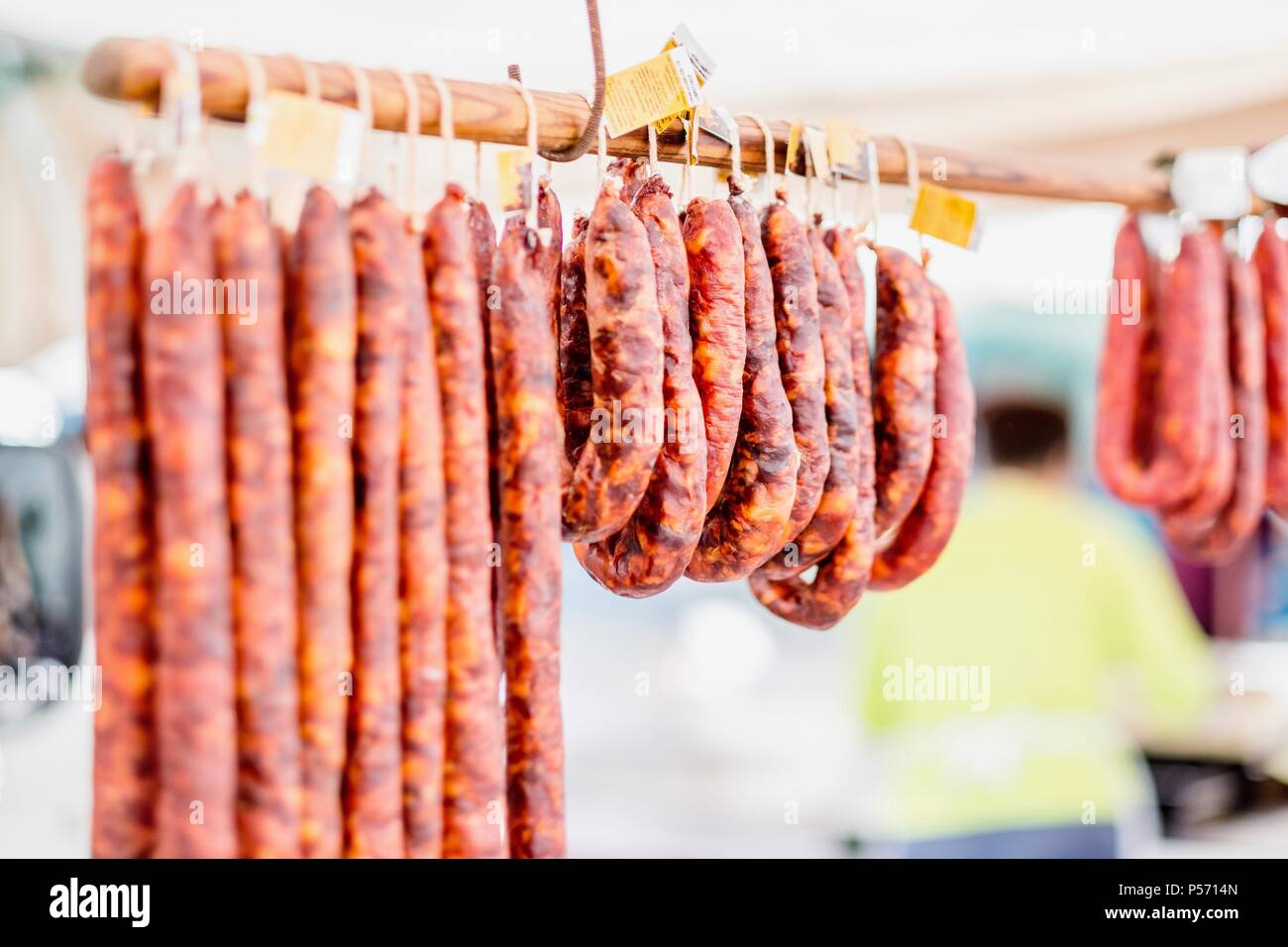 Many chorico sausages hunged on wooden stick at open air market in Portugal - Stock Image