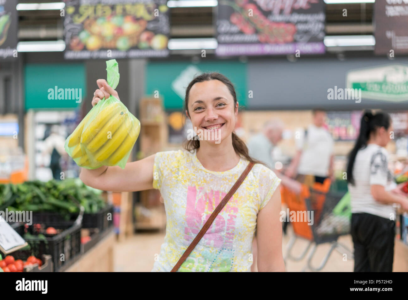 Happy girl bought bananas in the store. Smiling woman with bananas in hand. Blurry. - Stock Image