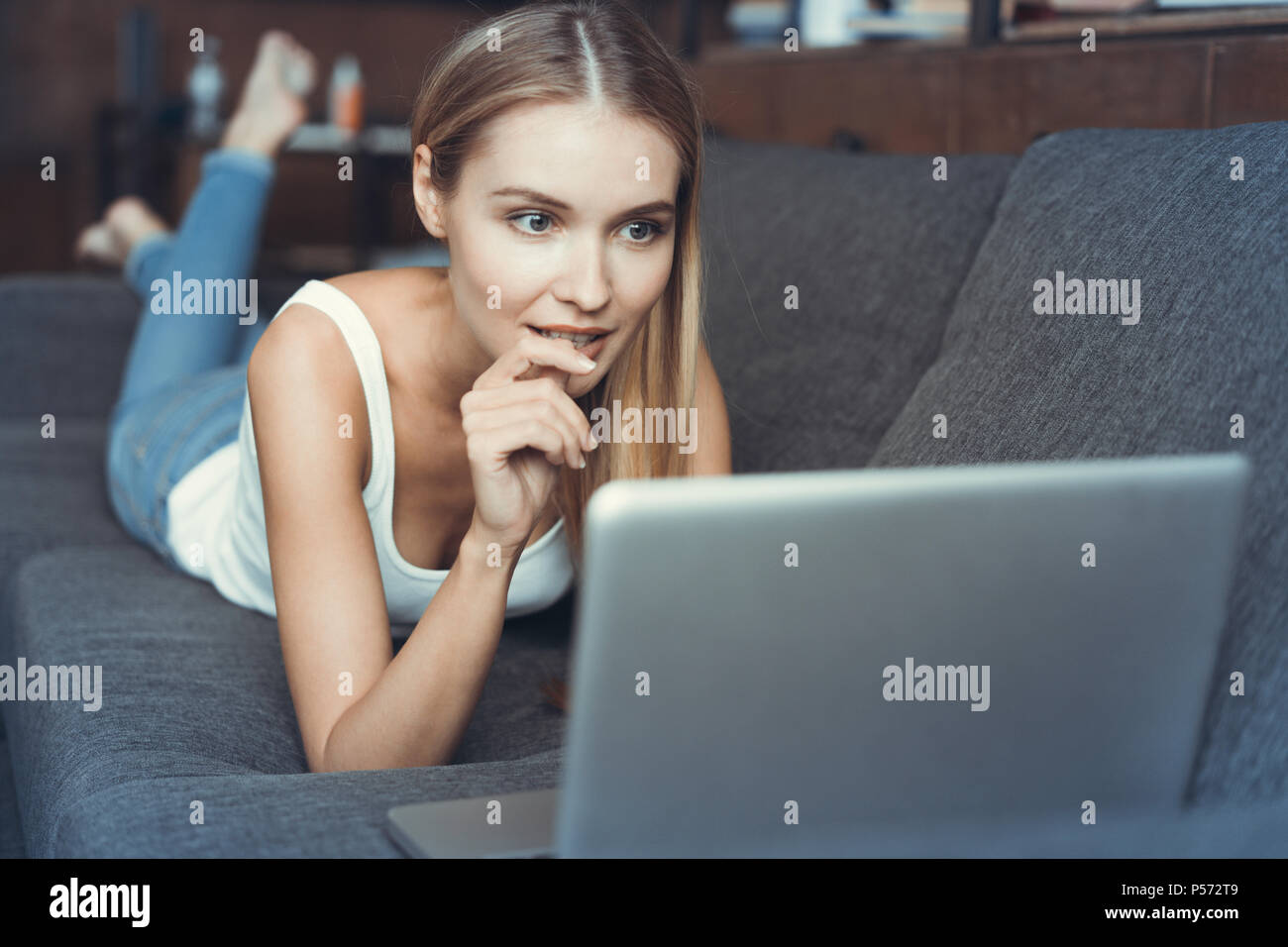 Casual young woman lying on couch and using laptop at home - Stock Image