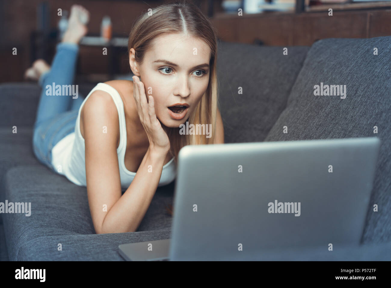 Casual young woman lying on couch and using laptop at home Stock Photo