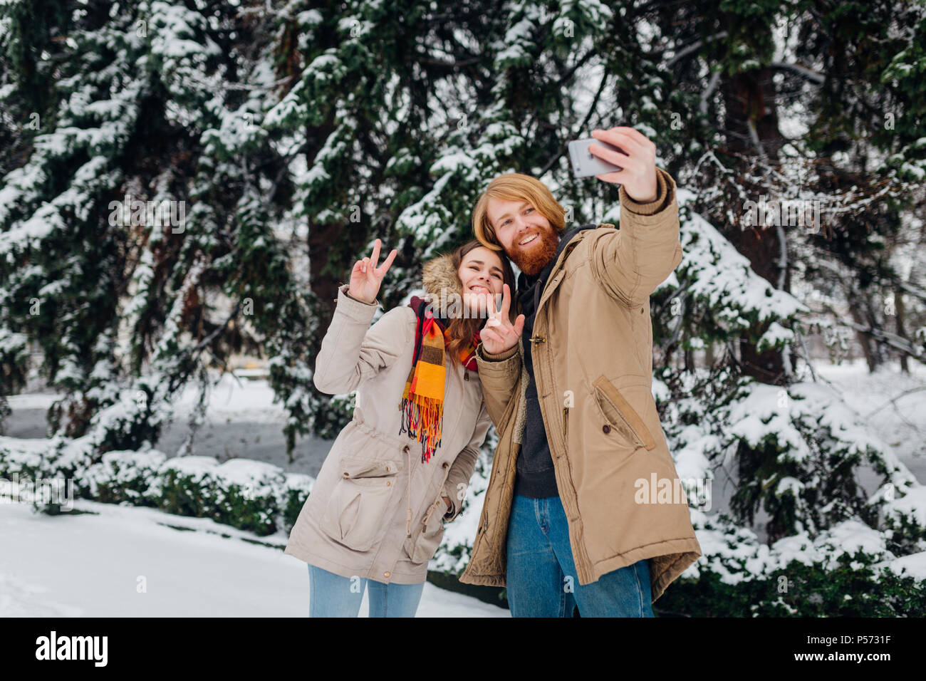Young couple in love make a hoto of themselves on mobile phone. shows gesture two thumbs up. The guy holds smartphone on elongated hand and makes self - Stock Image