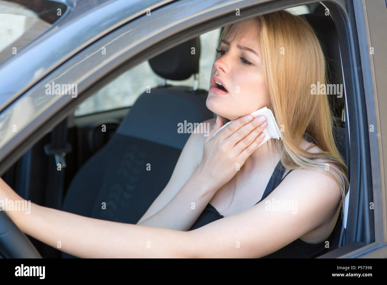 woman tired of heat in a car in summer - Stock Image